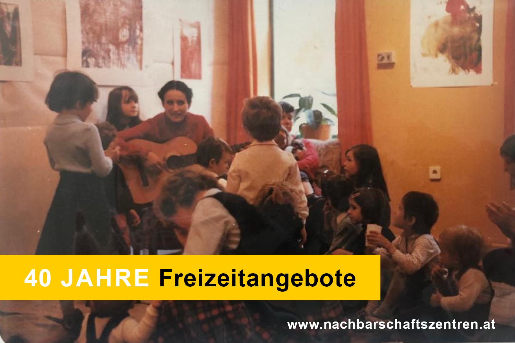 Eine Frau spielt auf der Gitarre. Kinder sitzen rundherum